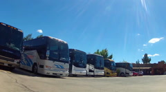 Camera Moving Toward Large Tour Buses In Parking Lot Stock Footage