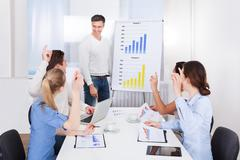 coworkers asking queries to team leader - stock photo