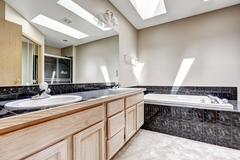bathroom with granite tile trim and skylight - stock photo