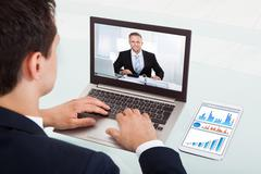 cropped image of young businessman video conferencing on laptop at desk in of - stock photo