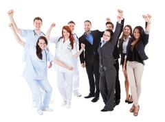 doctors and managers raising arms - stock photo