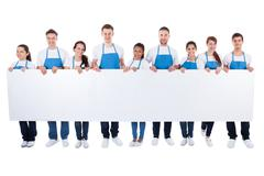 group of cleaners holding a blank white banner - stock photo
