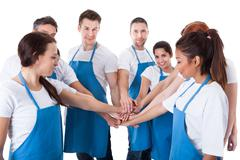 cleaners stacking hands - stock photo