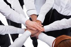 Waiters and waitresses stacking hands Kuvituskuvat