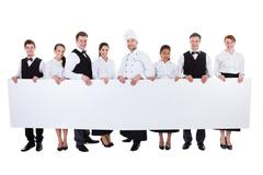 group of catering staff holding a blank banner - stock photo