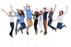 group of diverse people raising arms and jumping - stock photo