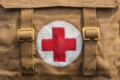 Red cross medical aid symbol on an old army bag Stock Photos