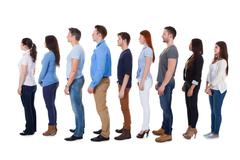 diverse group of people standing in row - stock photo