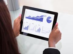 Businesswoman analyzing financial charts on digital tablet Stock Photos