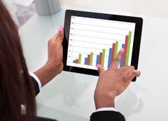 Businesswoman analyzing comparison graph on digital tablet at desk Stock Photos