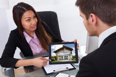 Businesswoman showing digital tablet to male colleague with house photo Stock Photos