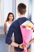 rear view of young man hiding bouquet from woman at house doorway - stock photo
