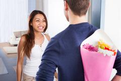 Rear view of young man hiding bouquet from woman at house doorway Stock Photos