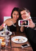 Smiling young couple taking self portrait through smartphone at restaurant ta Stock Photos