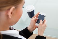 Close-up of woman using mobile phone in front of disposal cup Stock Photos
