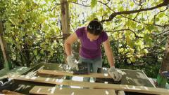 DIY - woman sanding wood planks with electric sand machine Stock Footage