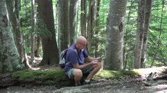 Tourist Man Resting Mountain Forest Trip Sitting Use Tablet Accessing Internet - stock footage