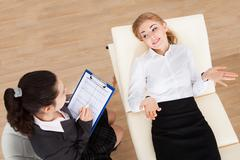 Young female psychiatrist holding clipboard examining businesswoman Stock Photos