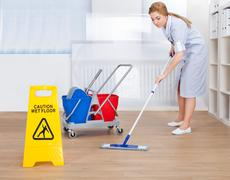 portrait of young maid cleaning floor with mop - stock photo