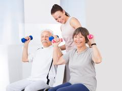 Young female trainer assisting senior couple with dumbbells at healthclub Kuvituskuvat