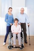 portrait of female caregiver with disabled senior couple at nursing home - stock photo