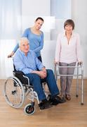portrait of disabled senior couple with female caregiver at nursing home - stock photo