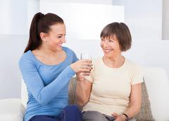 female caregiver giving glass of water to senior woman at nursing home - stock photo