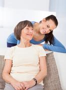 Portrait of happy young female caregiver with senior woman in nursing home Stock Photos