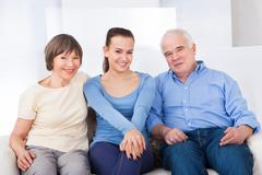 portrait of happy female caregiver with senior couple at nursing home - stock photo
