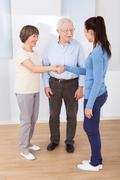 young female caregiver shaking hands with senior couple at nursing home - stock photo