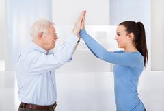 Side view of happy female caregiver and senior man giving high five at nursin Stock Photos