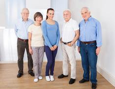 Full length portrait of female caregiver with senior people standing at nursi Stock Photos