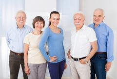 Portrait of confident female caregiver with senior people standing at nursing Stock Photos