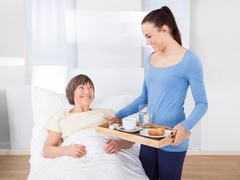 Female caregiver serving breakfast to senior woman at nursing home Stock Photos