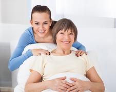 portrait of happy young female caregiver with senior woman in nursing home - stock photo