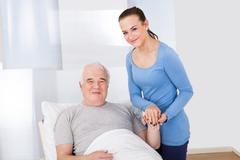 portrait of young female caregiver comforting senior man at nursing home - stock photo