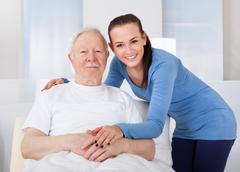 young female caregiver consoling senior man at nursing home - stock photo