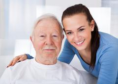 Portrait of young female caretaker with senior man at nursing home Stock Photos