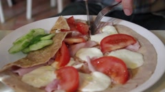 Stock Video Footage of man's hands eat savoury pancake with cheese tomato, cucumber and ham