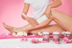 midsection of female therapist waxing customer's leg at beauty spa - stock photo