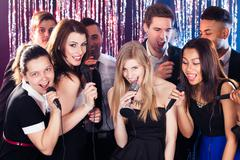 friends singing into microphones at karaoke party - stock photo