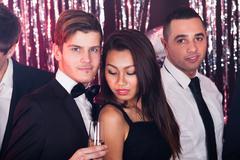 Men dancing with woman in nightclub Kuvituskuvat