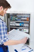 cropped image of male technician analyzing blueprint in front of fusebox - stock photo