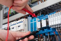 closeup of male electrician examining fusebox with multimeter probe - stock photo