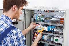 Side view of male technician examining fusebox with digital insulation resist Stock Photos