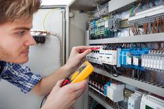 side view of male technician examining fusebox with digital insulation resist - stock photo