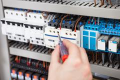 cropped image of male electrician examining fusebox with screwdriver - stock photo