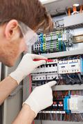 cropped image of male electrical engineer examining fusebox with multimeter p - stock photo