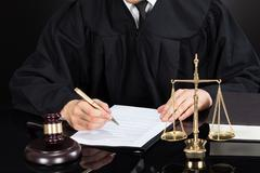 Midsection of male judge writing on paper at desk against black background Stock Photos