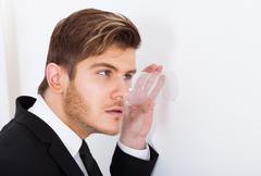 young businessman with glass on wall eavesdropping in office - stock photo